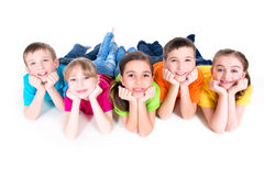 Five beautiful kids lying on the floor. Five beautiful smiling kids lying on the floor in bright colorful t-shirts - isolated on white stock images