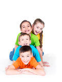 Five beautiful kids lying on the floor. Five beautiful smiling kids lying on the floor in bright colorful t-shirts -  isolated on white Stock Photo
