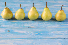 Five beautiful ripe pears on a blue wooden table. Ripe pears in a basket on a rustic wooden table. The concept of healthy eating with natural products Royalty Free Stock Photos
