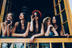 Five beautiful young girls. Look out from the window Stock Photos