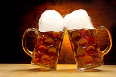 Five Beer Glasses on the Wooden Table. Five Big Glasses of Beer Standing on the wooden Table on the Wooden Background Royalty Free Stock Image