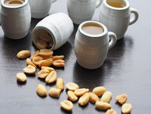 Five beer mugs and one mug with nuts on a wooden table stock photo