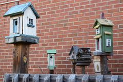 Five birdhouses with a brick wall background. And fence in foreground royalty free stock photography
