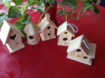 Five Birdhouses. Red table,  five miniature birdhouses, unpainted, trailing ivy, outdoors, craft time Royalty Free Stock Photos
