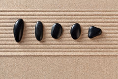 Five black pebbles on raked sand. Five black pebbles on a raked sand zen garden Stock Photography