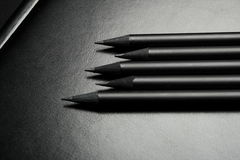 Five black pencils over black Royalty Free Stock Images