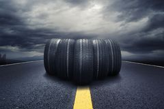 Five black tires rolling on a road with clouds Stock Photography