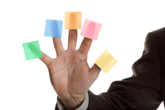 Five blank adhesive note reminders. Businessman holds up five blank multi coloured stickies, one on each finger ready for text messages stock photo