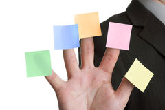 Five blank adhesive note reminders. Businessman holds up five blank multi coloured stickies, one on each finger ready for text messages royalty free stock image