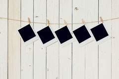 Five 5blank photo frame hanging on white wood background with stock photography