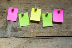 Five blank sticky notes on wooden wall Stock Image