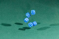 Five blue dices falling on a green table. Five blue dices falling on a isolated green table stock photo
