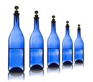 Five blue glass bottles with water Stock Image