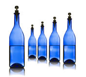 Five Blue Glass Bottles With Water On A White