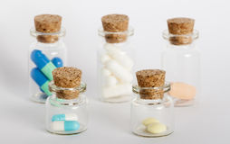 Five bottles with colorful pills. Five glass bottles with colorful pills and coks Royalty Free Stock Photography