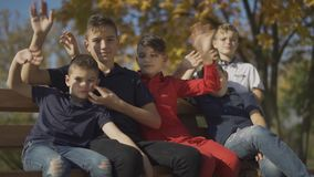 Five boys sitting on the bench and wave their hands on the camera. Friends spend time in big company outdoors. stock video footage