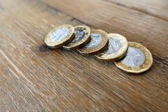 Five British UK pound coins on a wooden table.  Stock Images