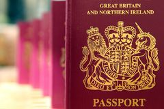 Five British United Kingdom European Union Biometric passports q. Ueueing in a line in shallow focus Stock Photos