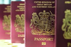 Five British United Kingdom European Union Biometric passports s. Tanding in a queue in shallow focus Stock Image