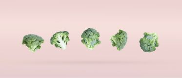 Five broccoli soar freely on a pink background casting a slight shadow.