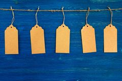 Five brown blank paper price tags or labels set hanging on a rope on the blue background. Royalty Free Stock Photos