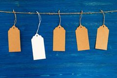 Five brown and white blank paper price tags or labels set hanging on a rope on the blue background. Royalty Free Stock Image