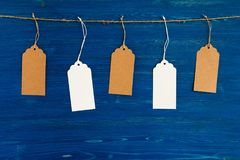 Five brown and white blank paper price tags or labels set hanging on a rope on the blue background. Royalty Free Stock Photography