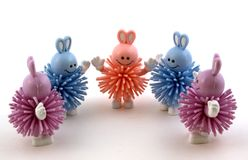 Five bunny toys in a half circle. Two purple, two blue and one pink royalty free stock photography