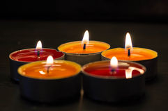 Five burning candles against a dark background Stock Images