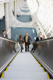 Five business people ascending escalator, smiling, front view, portrait, elevated view Stock Photo