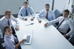 Five business people having a business meeting at the table in the office, looking at camera Stock Photo