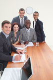 Five business people in a meeting. Smiling at the camera all together royalty free stock images
