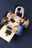 Five business people meeting. Businesspeople gathered around a table for a meeting, brainstorming. Aerial shot taken from directly above the table royalty free stock images