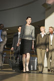 Five business people walking in airport terminal with luggage in tow, smiling, front view (surface level) Royalty Free Stock Photo