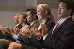 Five businesspeople applauding and smiling. Business people applauding in a presentation room