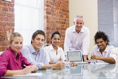 Five businesspeople in boardroom with laptop. Looking at camera stock image