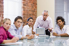 Five businesspeople in boardroom with laptop stock images