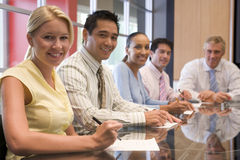 Five businesspeople in boardroom smiling. At camera stock image