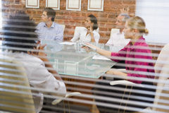 Five businesspeople in boardroom through window stock photography
