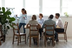 Five diverse professionals sitting in conference room listening. Five businesspeople gathered together for business training attentive listening mixed race coach stock image