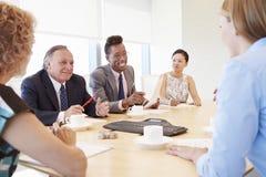 Five Businesspeople Having Meeting In Boardroom Stock Photo