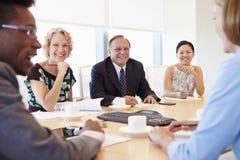 Five Businesspeople Having Meeting In Boardroom Stock Images