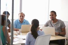 Five Businesspeople Having Meeting In Boardroom Stock Photos