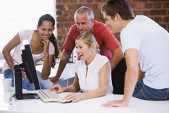Five businesspeople in office space. Looking at a computer stock images