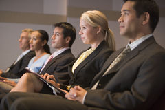Five businesspeople sitting in presentation. Business people applauding and smiling in a presentation room