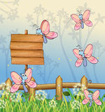 Five butterflies near an empty board Royalty Free Stock Image
