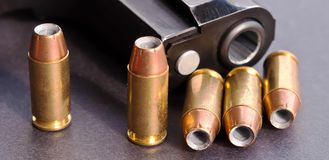 Five hollow point bullets next to a black pistol stock images