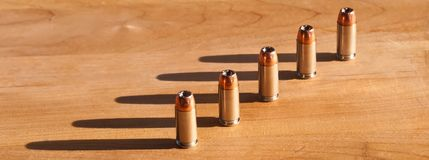 Five 40 caliber bullets. Five 40 caliber hollow point bullets on a wooden table with sunlight casting shadows behind them Royalty Free Stock Image
