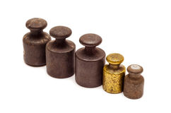 Five calibration weights in row. Set of five antique calibration weights in row, one gold, isolated on white background Royalty Free Stock Image
