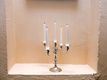 Five candles. Five candles on a candlestick standing in a wall Royalty Free Stock Images